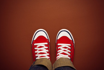 Feet From Above, Teenager in Sneakers Standing on Brown Backgrou