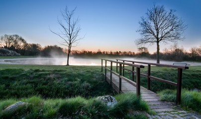 A wooden foot bridge at a misty lake during sunrise sunset