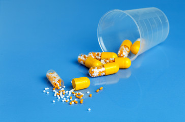 Yellow capsules with vitamins on a blue background