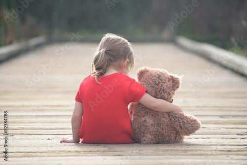 Leinwanddruck Bild Girl in red dress sitting with teddybear on boardwalk