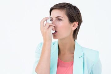 Pretty woman using her inhaler