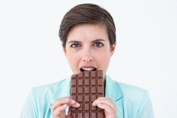 Happy brunette eating bar of chocolate