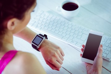 Woman using her smartwatch and phone