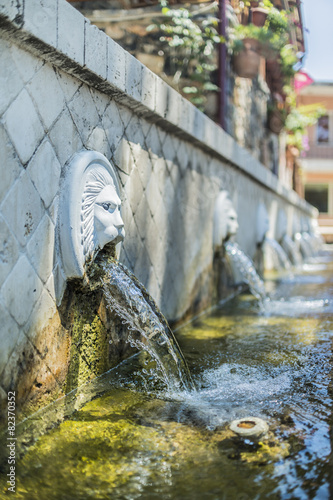 Leinwanddruck Bild Venetian fountain with lion heads in village of Spili. Crete.