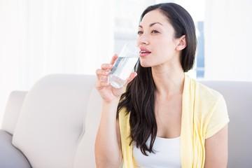 Pretty brunette drinking glass of water