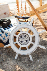 Decorative boat, binoculars and wheel on the beach