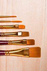 Varieties of painting brush on the wooden background.