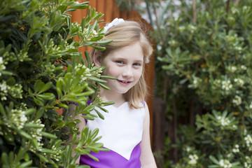 Niña rubia asomándose entre las plantas