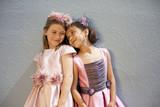 Niñas con vestidos de color rosa apoyando sus cabezas
