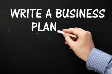 Write A Business Plan reminder on a Blackboard