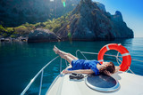 Woman lies on boat in blue dress. Leisure on yacht at sea
