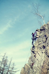 Retro filterd photo of female rock climber.