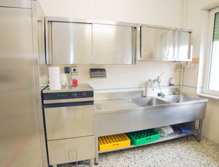 industrial kitchen with refrigerator, dishwasher and sink all st
