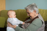 Elderly woman with a beautiful baby at home.