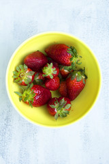Bowl of fresh strawberries on the white, wooden table