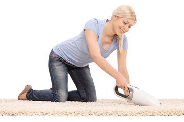 Woman cleaning a carpet with handheld vacuum cleaner