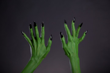 Green monster hands with sharp black nails, body-art