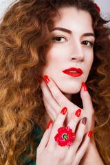 Кудрявая девушка с красными губами и украшениями