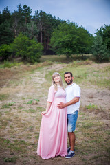 man and pregnant woman in nature, amid the pine forest