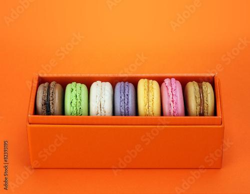 Papiers peints Macarons Macaroon in the orange box on orange background. Dessert