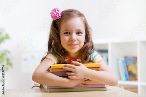 Leinwanddruck Bild Cute child girl preschooler with books