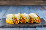 Mexican tacos with meat, beans, avocado, cheese and tomato sauce