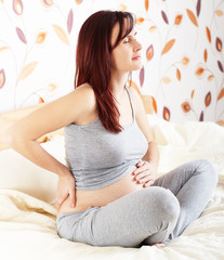 Pregnant woman sitting and  suffering from backache.