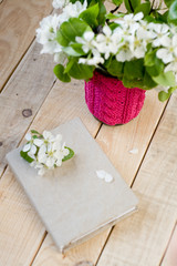 A bouquet of white spring flowers and vintage old notebook