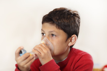 Young boy using inhaler on white background