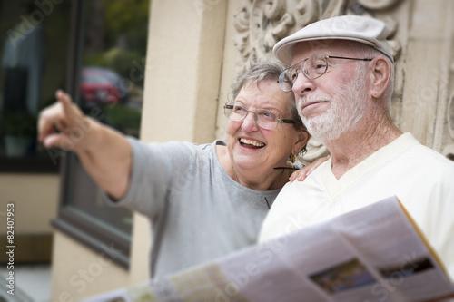 Leinwanddruck Bild Tourist Senior Couple Looking at Brochure Map