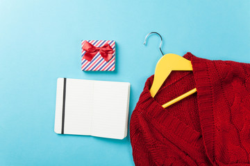 Gift box and notebook near hanger with sweater