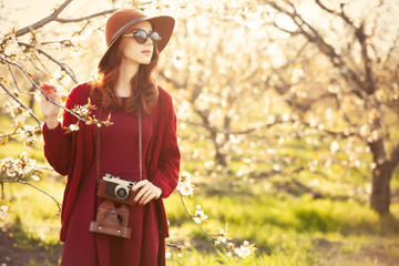 women with camera in blossom apple tree garden