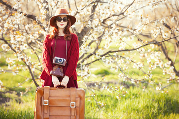 women with suitcase in blossom apple tree garden