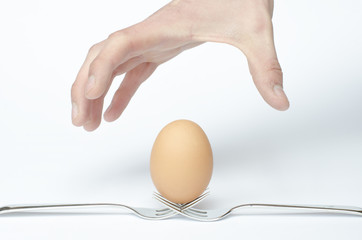 human hand attack on an egg and white background