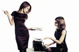 Two young fashion woman with a book and vintage typewriter