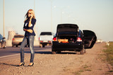 Fashion woman next to broken car calling on cell phone