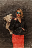 Glamour girl with a teddy bear on the background of the city