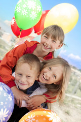 Group portrait of three laughing children with balloons outdoor