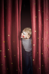 Boy Dressed Up as Clown Peeking Thru Stage Curtain