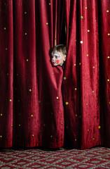 Boy Clown Peering Through Stage Curtains