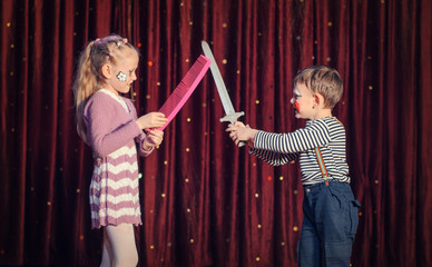 Boy and Girl Having Pretend Sword Fight on Stage