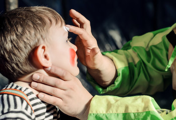 Man applying face paint to a little boy