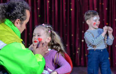 Young Girl Applied with Clown Makeup by an Artist