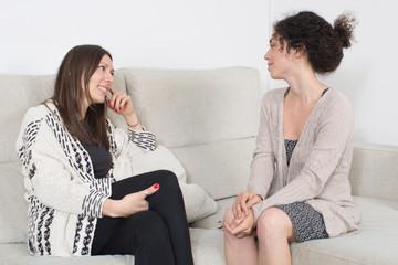 Zwei Schwestern unterhalten sich auf Sofa
