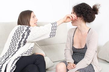 Frau reinigt das Auge einer Freundin