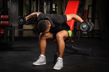 Young man doing Seated Bent Over Dumbbell Reverse Fly workout in