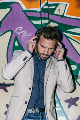 Elegant Young Man with Headphones Against a Graffiti Wall