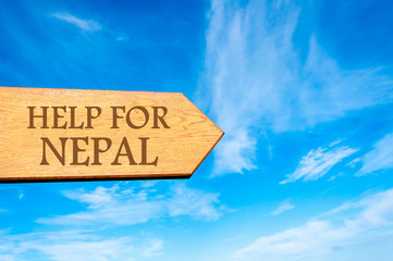 Wooden arrow sign with message HELP FOR NEPAL