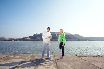 Two young athletes preparing for jogging by the river