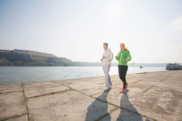 Young couple jogging by the Danube river on a nice sunny day